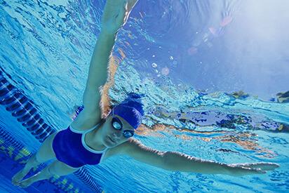 Frau mit Schwimmbrille taucht im Wasserbecken